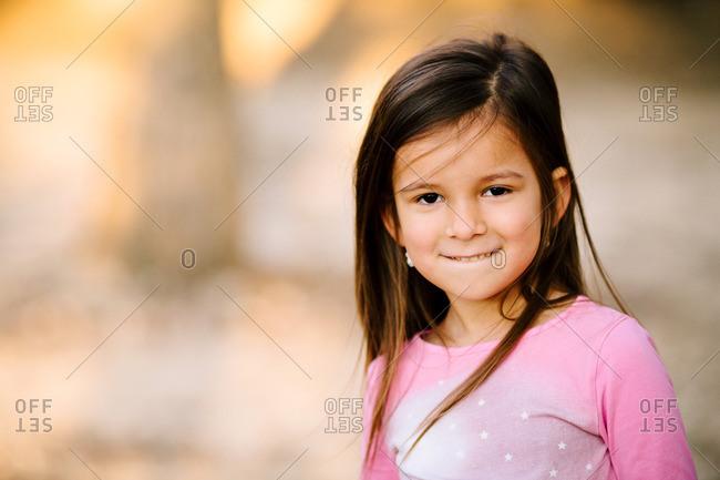 Little girl in a pink shirt biting her lip