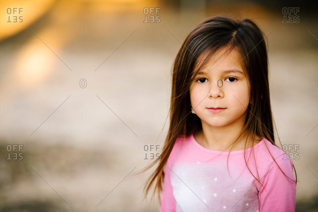 Little girl in a pink shirt making a serious face