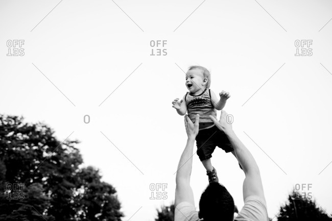 Father throwing his baby son into the air