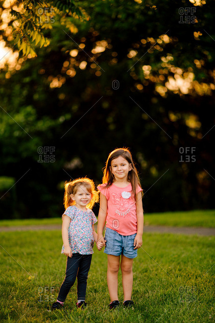 Two sisters standing together and holding hands in a park