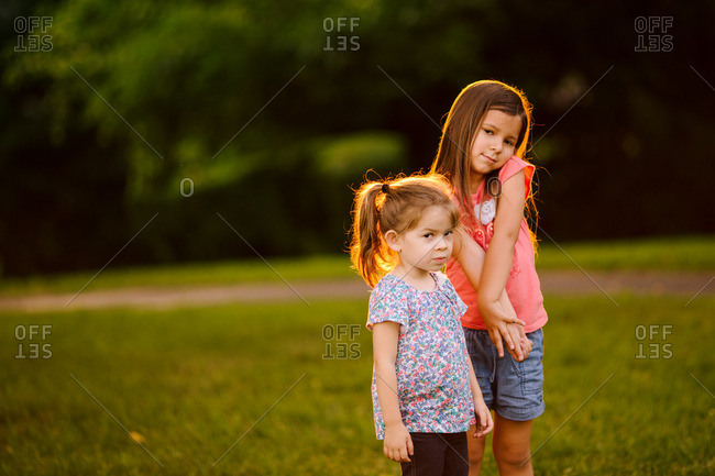 Two sisters standing together in a park