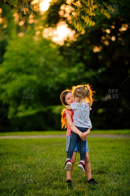 Girl holding her younger sister and hugging in a park