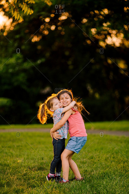 Two sisters hugging each other in a park