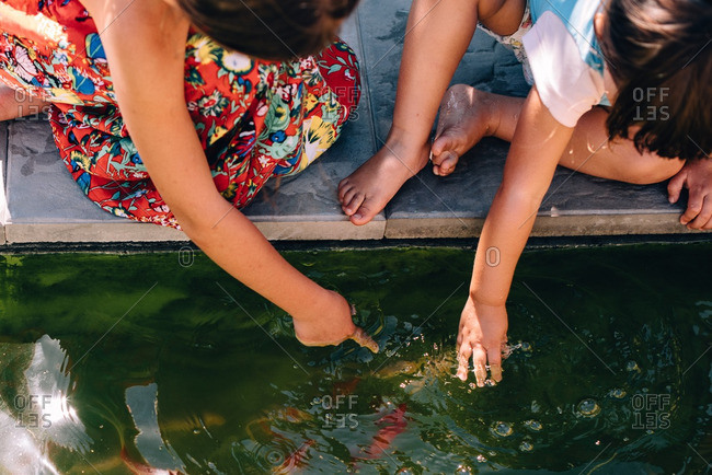 Woman and child play at edge of fish pond