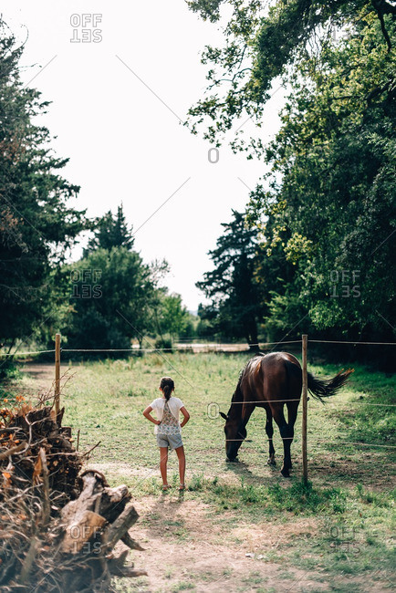 Young girl standing with hands at hips by horse pen