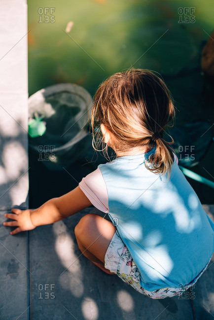 Young child with net scooping leaf from pool