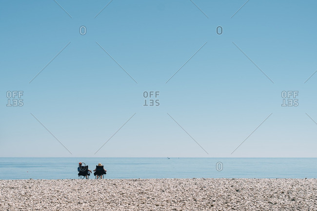 Two people sitting in chairs on beach