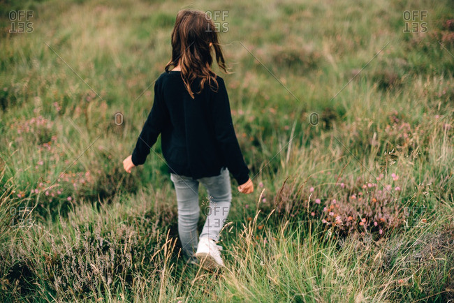 Young girl walking through field with wildflowers