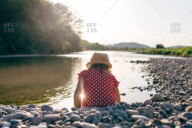 Young girl sitting on riverbank of pebbles at dusk