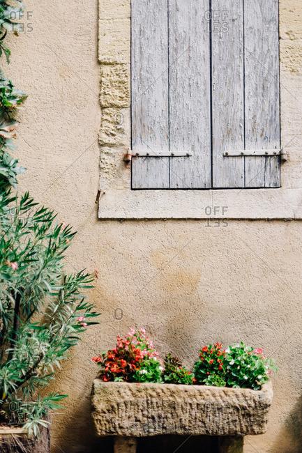 Stone planter under rustic wood shuttered window