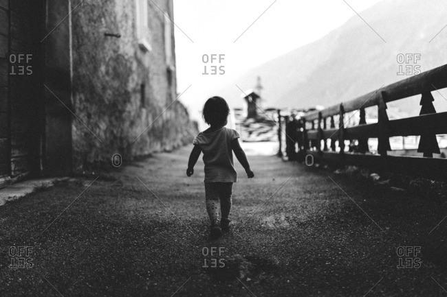 Toddler walking up path in rustic village