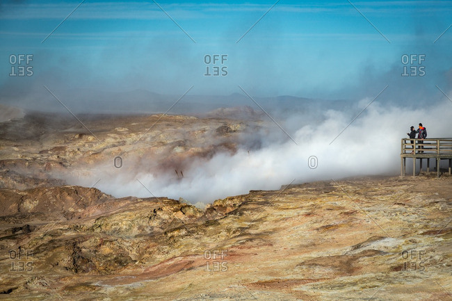 Two people on boardwalk overlooking Icelandic geothermal site with steam rising