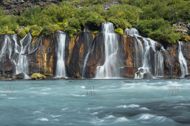Icelandic waterfalls falling into fast-flowing glacial river