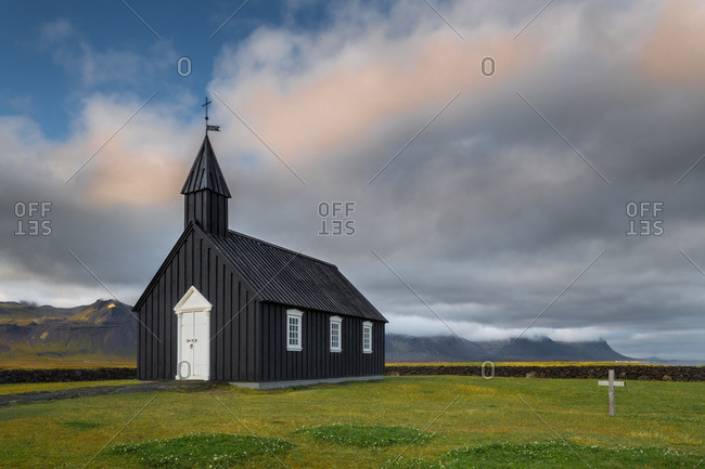 Black wooden church in remote Icelandic location with evening sky