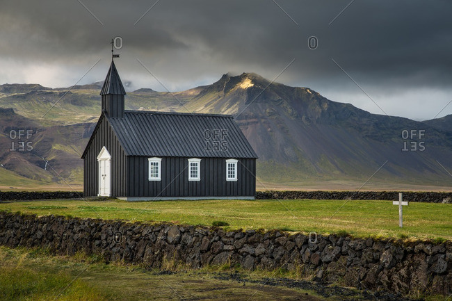 Black wooden church in remote Icelandic location with stormy sky
