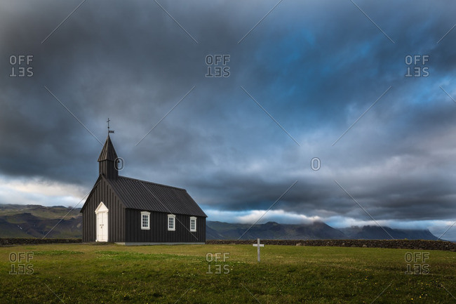 Black wooden church in remote Icelandic location with storm clouds