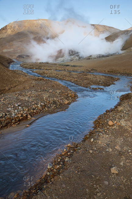 Steam rising along a river in Icelandic geothermal landscape in the remote Kjoslur highlands