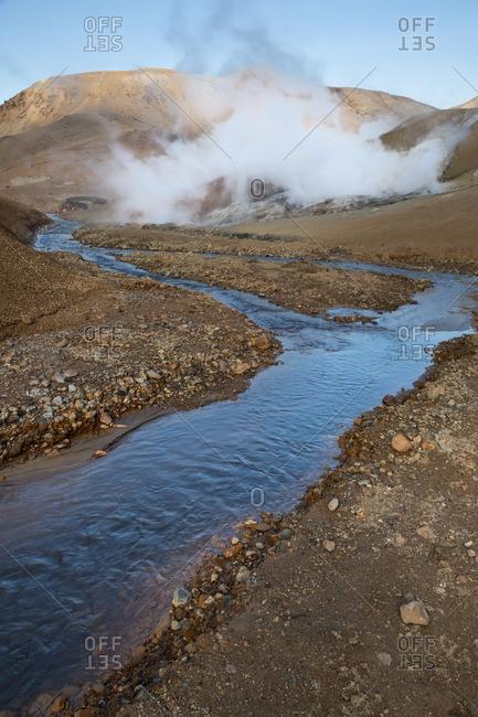 Steam rising along a river in Icelandic geothermal landscape in the remote Kjoslur highlands