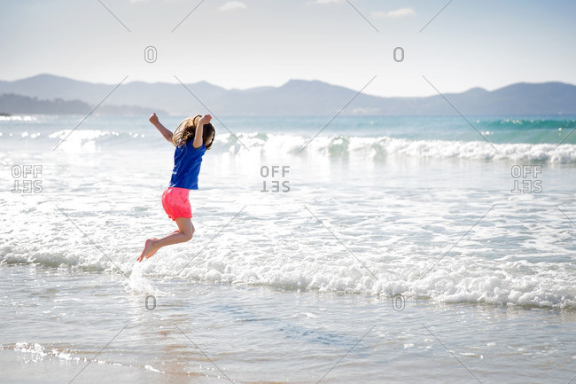 Girl jumping into the waves along the beach