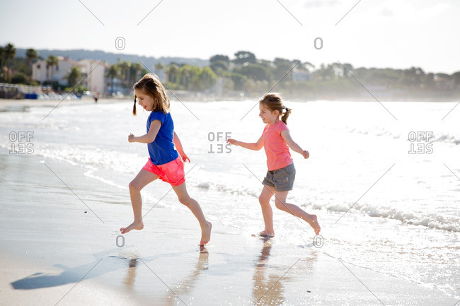Two girls play together along the beach