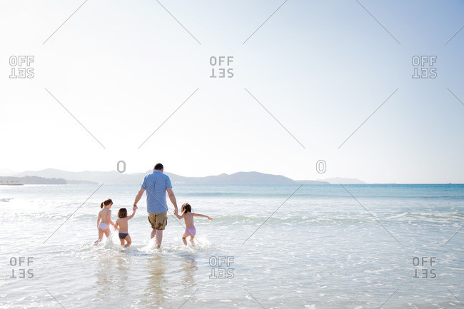 Family wading into the surf together