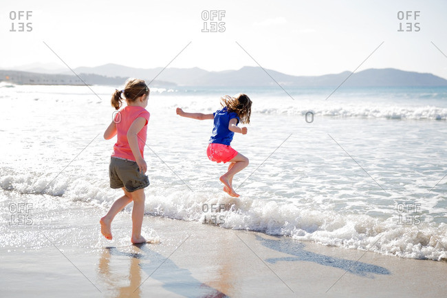 Girls jumping into the waves along the beach