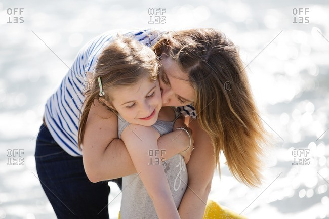 Mother cuddling with her daughter along a beach