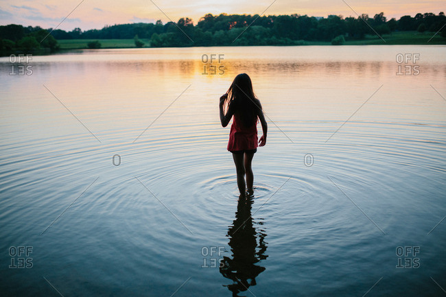 Silhouette of a girl wading into a lake at sunset