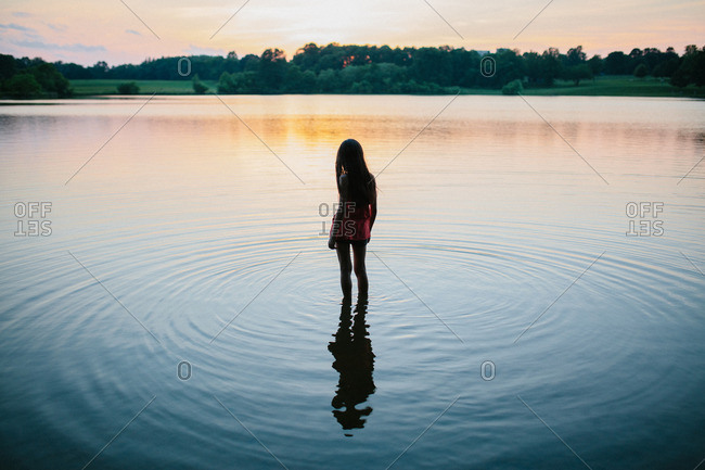 Silhouette of a girl wading into a lake at dusk