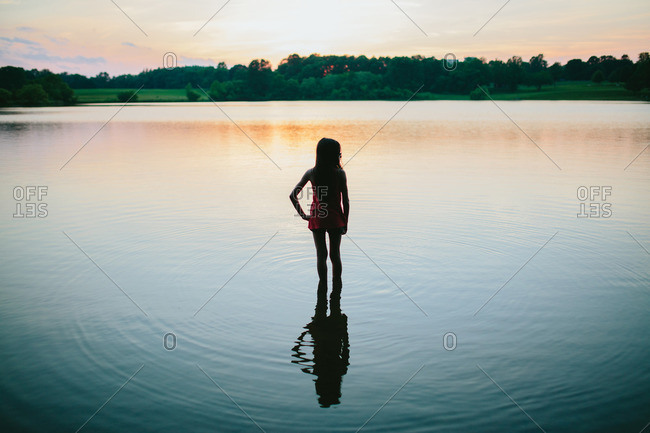 Silhouette of a girl wading into a lake in the early evening