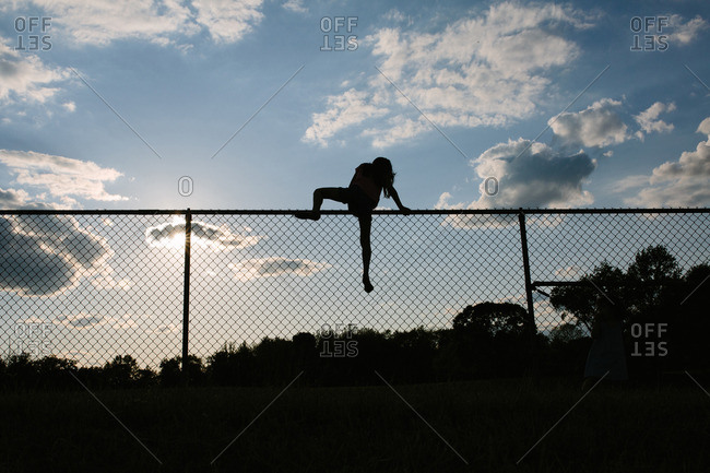 Silhouette of a child climbing over a fence