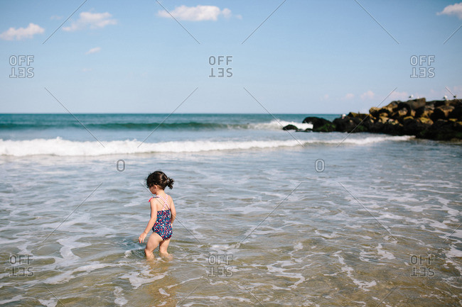 Girl wading into the surf along the beach