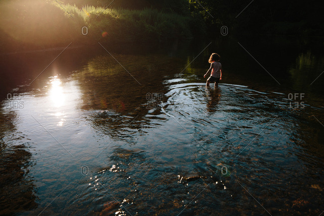 Child wading into a lake at sunset