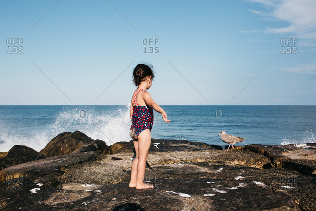 Girl standing on a rocky beach next to crashing waves