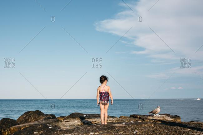 Girl standing on a rocky beach