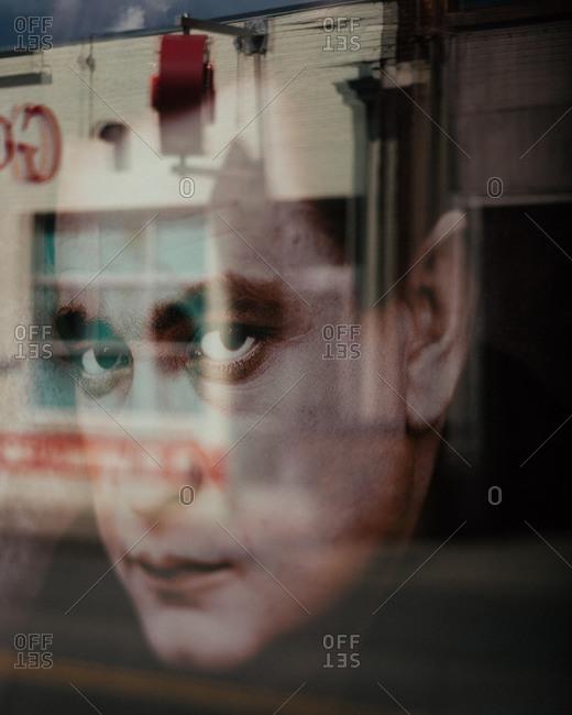 Nashville, TN - August 11, 2016: Portrait of man's face in window reflection