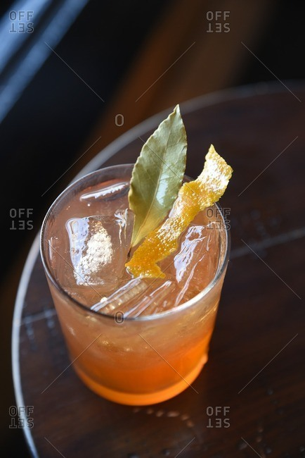 Overhead view of a cocktail with bay leaf and orange rind