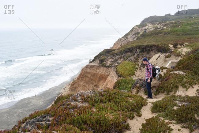San Francisco, California - July 24, 2016: Man in backpack hiking on seaside cliff