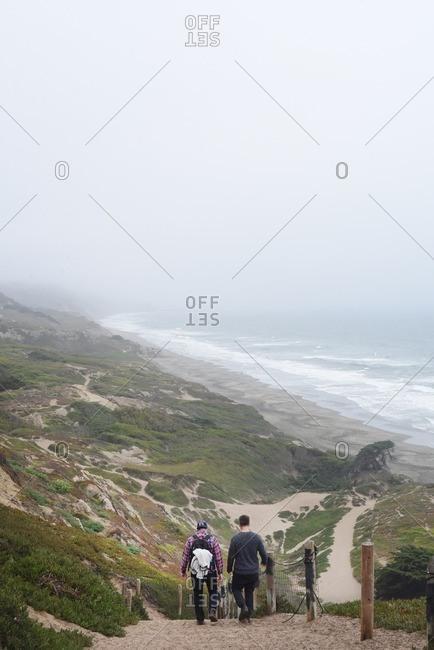 San Francisco, California - July 24, 2016: Two men hiking on seaside cliffs