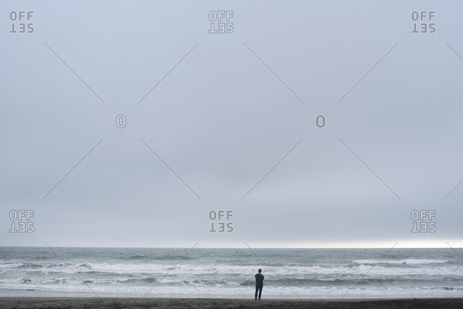 Man standing on beach and gazing at sea