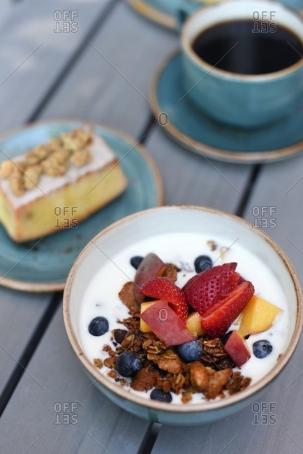 Bowl of granola with fruit and milk, breakfast pastry and coffee