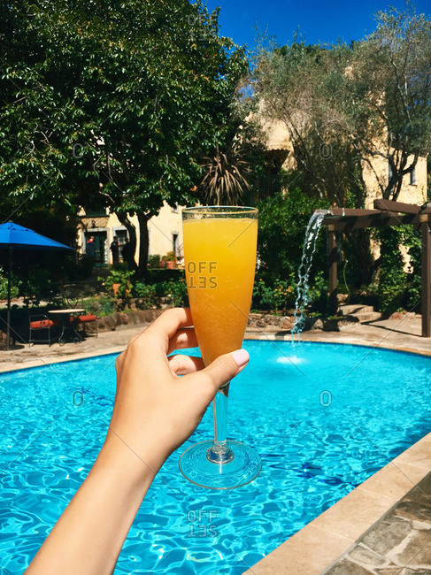 Woman's hand with mimosa cocktail toasting at luxury pool area of resort