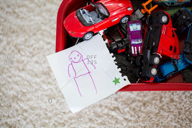 Child's drawing on a piece of paper set on top of a bin full of toy cars