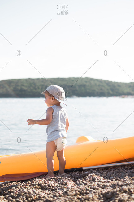 Toddler boy standing near the lakeshore next to a boat and oar