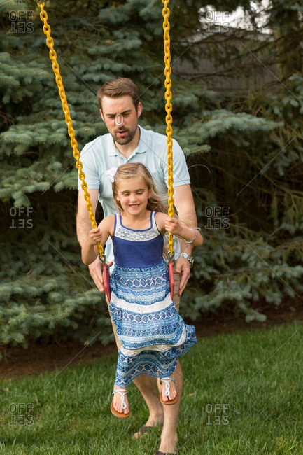 Father pushing daughter on a swing