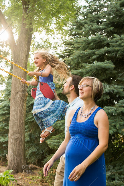 Mother standing by her husband pushing their daughter on a swing