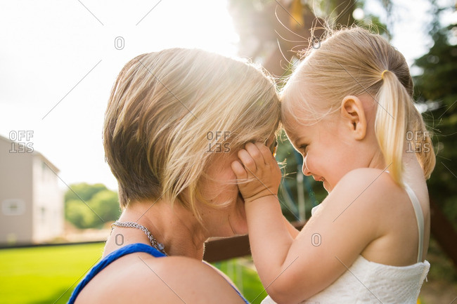 Mother holding her daughter face to face outdoors