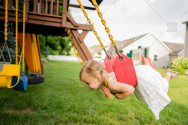 Little girl swinging on her belly on a swing