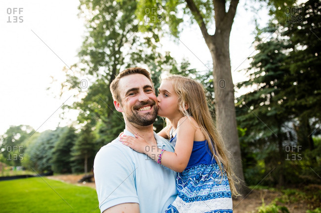 Girl kissing dad on cheek