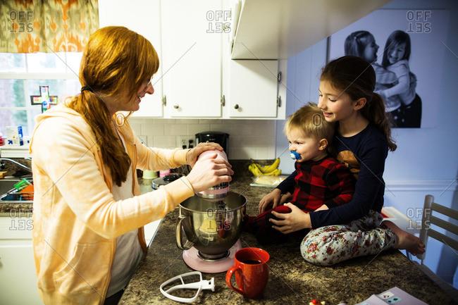 Children helping mother bake in their kitchen